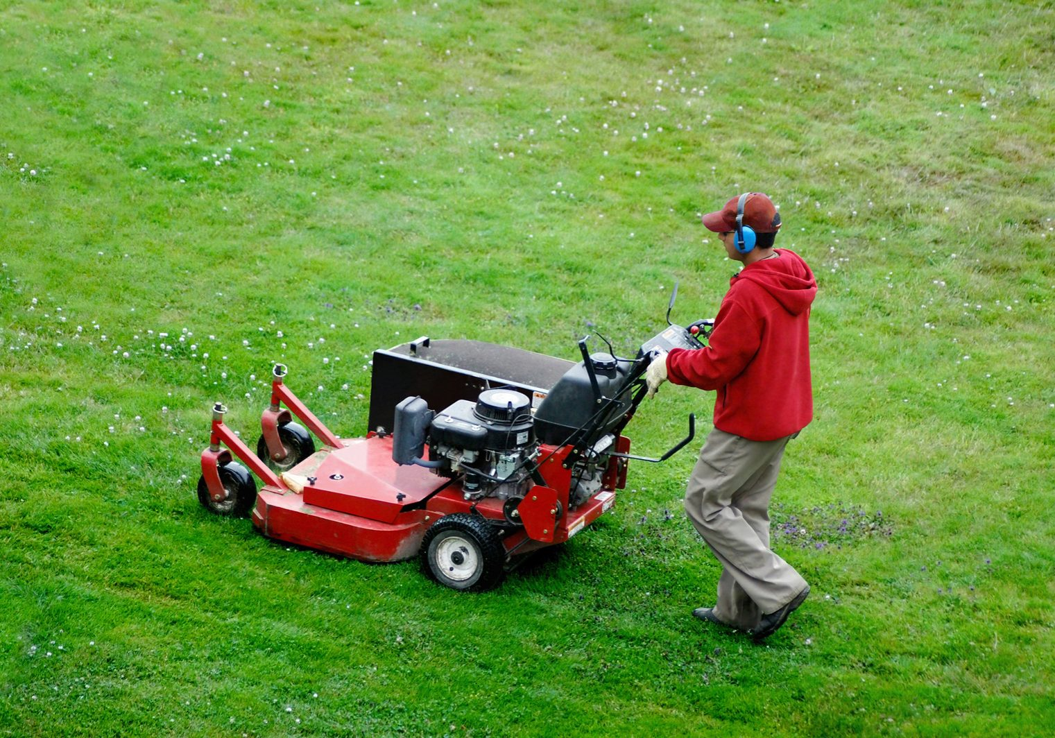 Man mowing the lawn with copy space